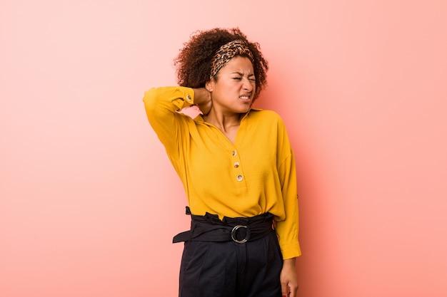 座りがちなライフスタイルのため首の痛みに苦しんでいるピンクの背景の若いアフリカ系アメリカ人女性。