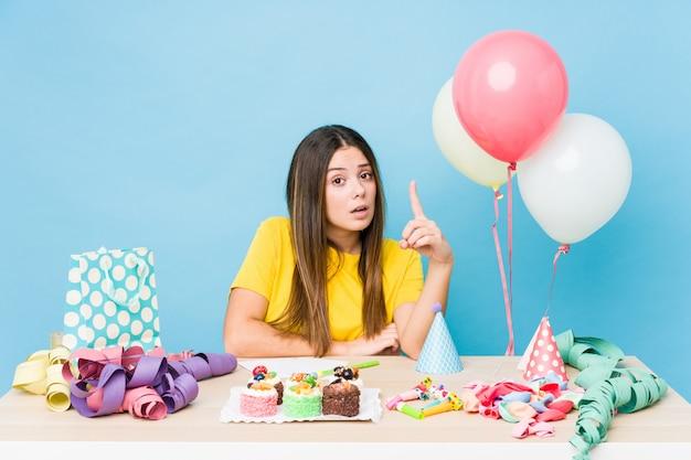 Молодая кавказская женщина организуя день рождения имея идею, концепцию воодушевленности.