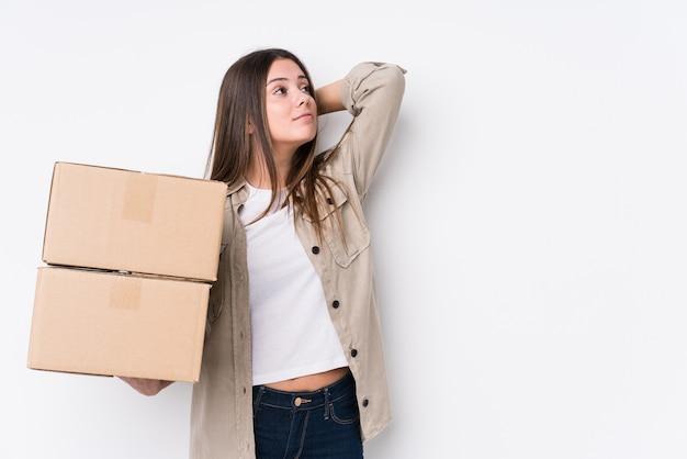 若い白人女性が頭の後ろに触れる新しい家に移動し、考えて、選択をします。