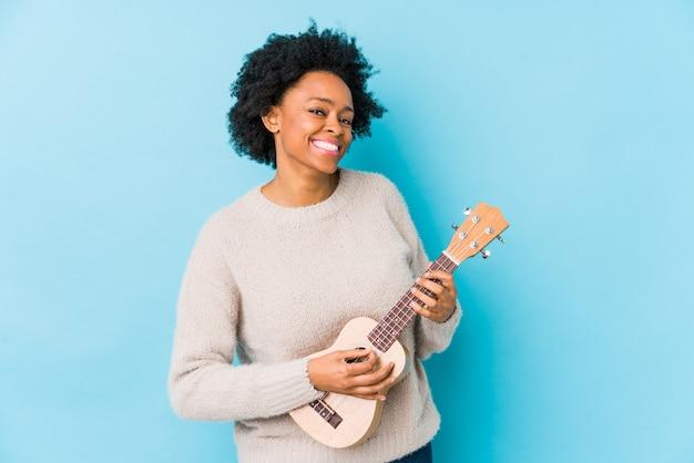 ウクレレを演奏若いアフリカ系アメリカ人女性は、幸せ、笑顔、陽気な分離しました。