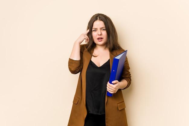 人差し指で失望のジェスチャーを示すファイルを保持している若いビジネス女性。