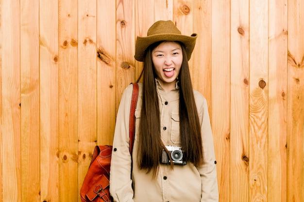 舌を突き出して面白いとフレンドリーな若い中国人旅行者の女性。