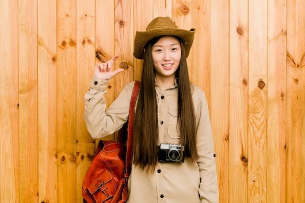 Молодой китайский путешественник женщина держит что-то немного с указательными, улыбаясь и уверенно.