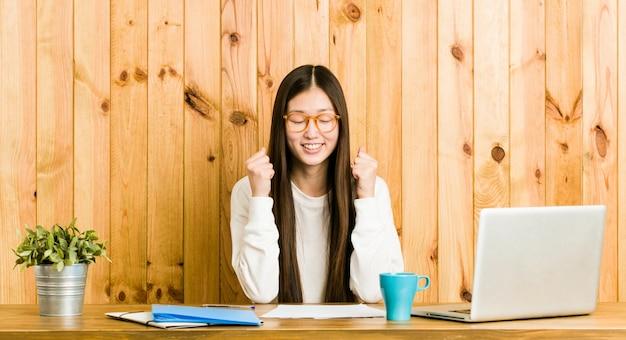 幸せと成功を感じて、拳を上げる彼女の机で勉強して若い中国人女性。