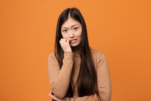 爪をかむ若いかなり中国人の女性、神経質で非常に不安。