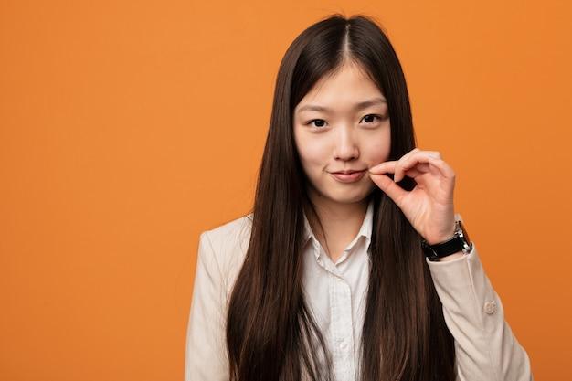 Молодая женщина дела китайская с пальцами на губах держа секрет.