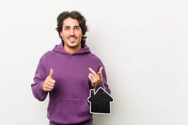 Молодой человек держит форму значок дома, улыбаясь и поднимая палец вверх