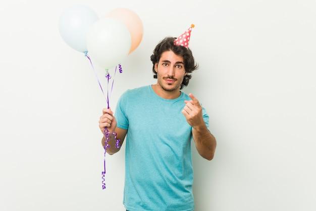 Молодой человек празднует вечеринку, держа воздушные шары, указывая пальцем на вас, как будто приглашая подойти ближе.