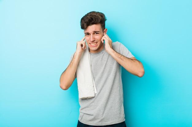 若いフィットネス男の手で耳を覆っています。