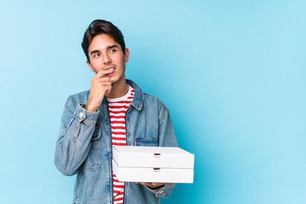 ピザを保持している若い白人男は、コピースペースを見て何かについてリラックスした思考を分離しました。