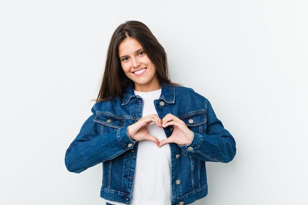 笑顔で手でハートの形を示す若いかわいい女性。