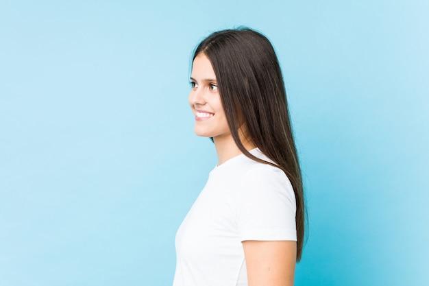 Молодой кавказский девушка лицо крупным планом, изолированных в синем