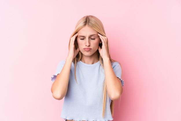 Молодая белокурая женщина на висках розовой предпосылки касающих и иметь головную боль.