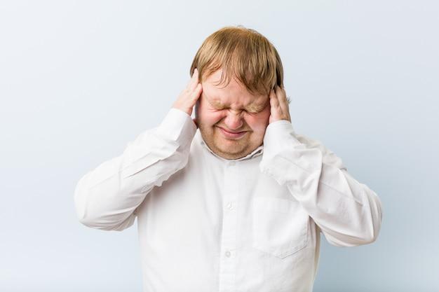 Молодой аутентичный рыжий толстый человек трогательно храмы и головная боль.