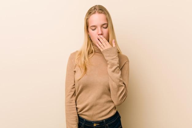 Милая и естественная женщина подростка зевая показывая утомленный жест покрывая рот рукой.