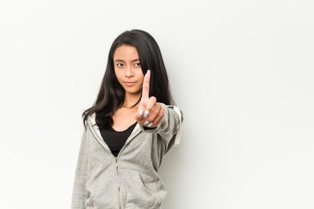Женщина молодого фитнеса китайская показывая номер один с пальцем.