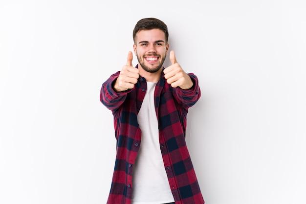 Молодой кавказский человек представляя в белой стене изолированной с большими пальцами руки поднимает, веселит о что-то, поддерживает и уважает концепцию.