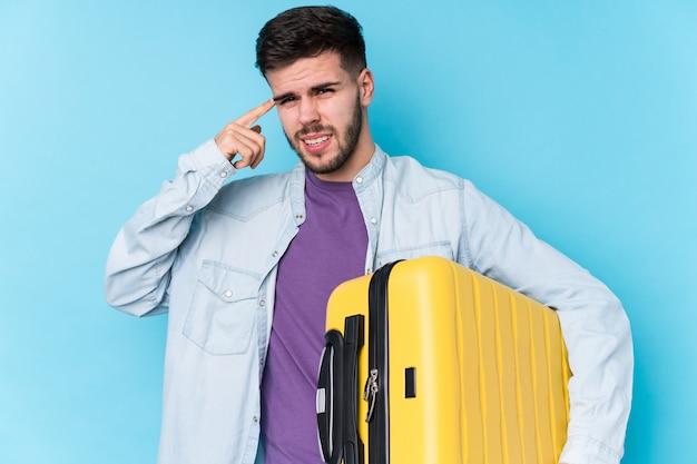 Молодой кавказский человек путешественника держа изолированный чемодан показывая жест разочарования с указательным пальцем.