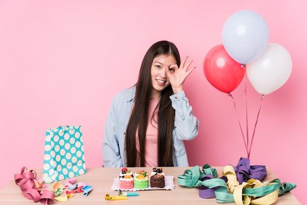 Молодая китайская женщина организовывая день рождения изолировала возбужденный держать одобренный жест на глазе.