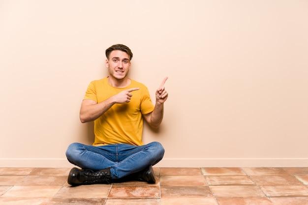 Молодой кавказский человек сидя на поле изолировал сотрясенный указывать с указательными пальцами к космосу экземпляра.