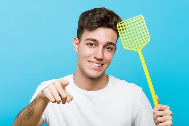 ハエを保持している若い白人男は前を向く陽気な笑顔をたたきます。