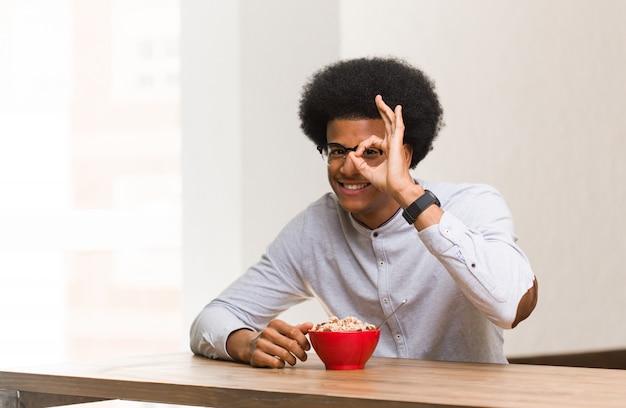 Молодой темнокожий мужчина, имеющий завтрак, уверенный, делающий хорошо жест на глазу