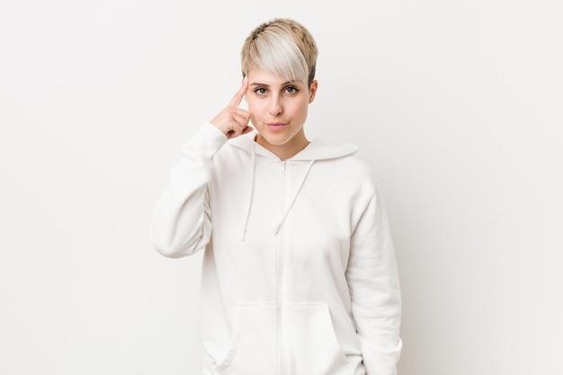 Молодая соблазнительная женщина носить белый балахон, указывая висок с пальцем, думая, сосредоточены на задаче.