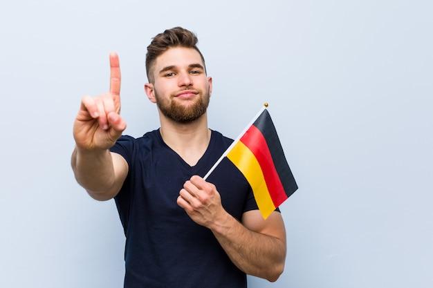 Молодой кавказский человек держа флаг германии показывая номер один с пальцем.