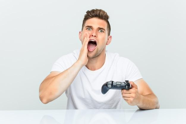 叫んでいるゲームコントローラーを保持している若い男は正面に興奮しています。