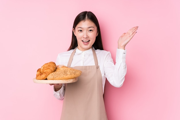 Молодая китайская женщина пекаря изолировала получать приятный сюрприз, взволнован и поднимать руки.