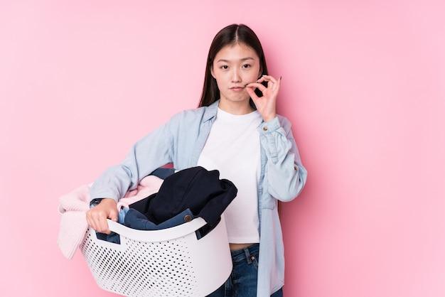 Молодая китайская женщина выбирая вверх пакостные одежды изолированные с пальцами на губах держа секрет.