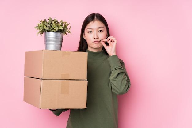 Молодая китайская женщина держа коробки изолированный с пальцами на губах держа секрет.