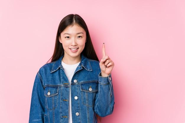 Молодая китайская женщина представляя в розовой стене изолировала показывать одно с пальцем.