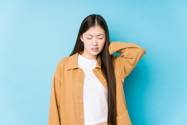 若い中国人女性が座りがちなライフスタイルのため首の痛みに苦しんで分離された青い壁でポーズします。