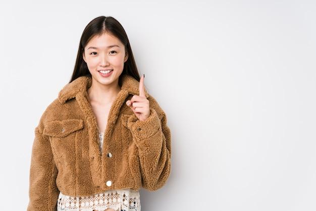 Молодая китайская женщина представляя в белой стене изолировала показывать одно с пальцем.