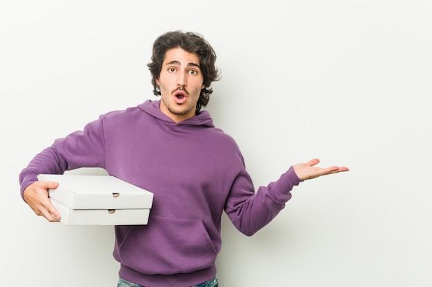 ピザのパッケージを保持している若い男は、手のひらにコピースペースを保持して感動しました。
