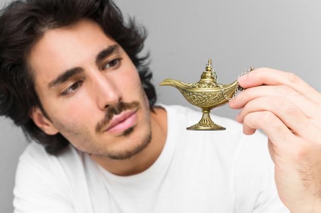 灰色の壁に分離された魔法のランプを保持している若い白人男