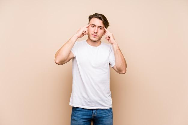 Молодой кавказский изолированный представлять человека сфокусировал на задаче, держащ указательные пальцы указывая голова.