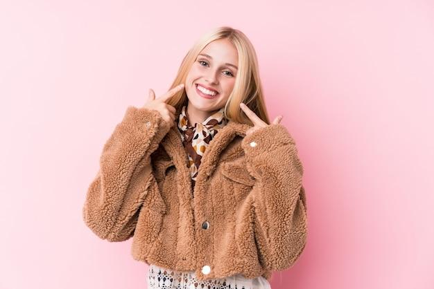 ピンクに対してコートを着ている若いブロンドの女性