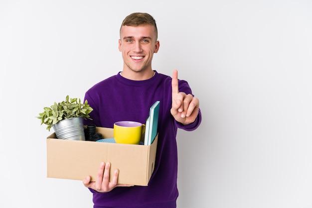 Молодой кавказский человек двигая к новому дому показывая номер один с пальцем.