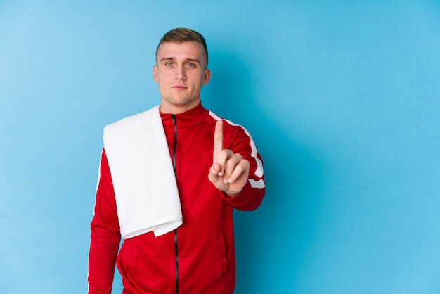 Молодой человек спорта показывая номер один с пальцем.