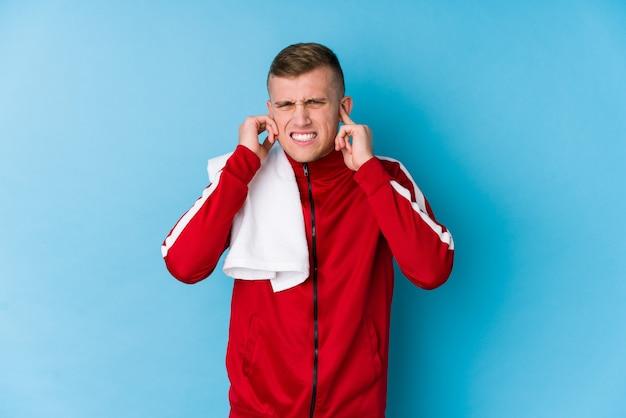 若いスポーツの男の手で耳を覆っています。