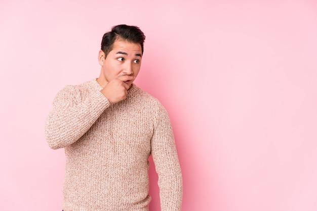 Молодой соблазнительный мужчина позирует в розовом