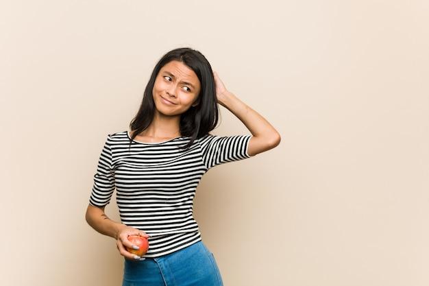 頭の後ろに触れる、考えて、選択をするリンゴを保持している若いアジア女性。