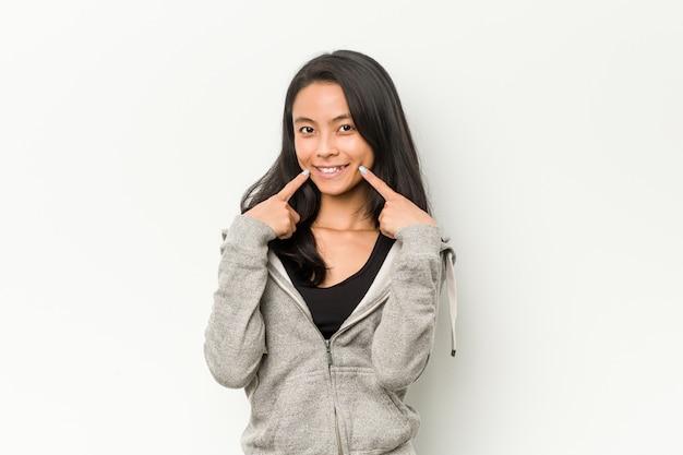 若いフィットネス中国の女性の笑顔、口に指を指しています。