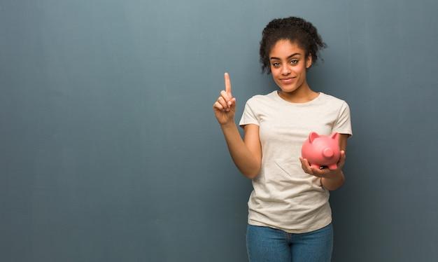Молодая черная женщина показывает номер один. она держит копилку.