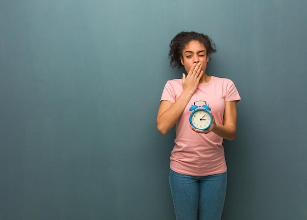 若い黒人女性は疲れていて非常に眠い。彼女は目覚まし時計を持っています。