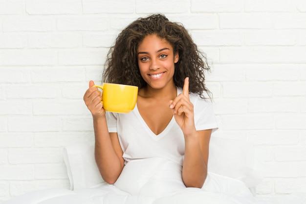 Молодая афро-американская женщина сидя на кровати держа показ одно кружки кофе с пальцем.