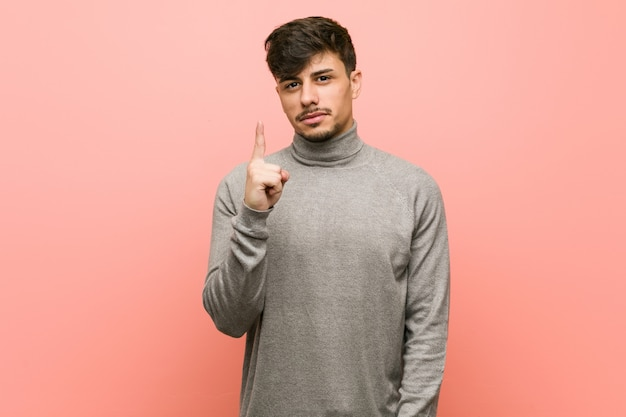 Молодой умный студент человек показывает номер один с пальцем.
