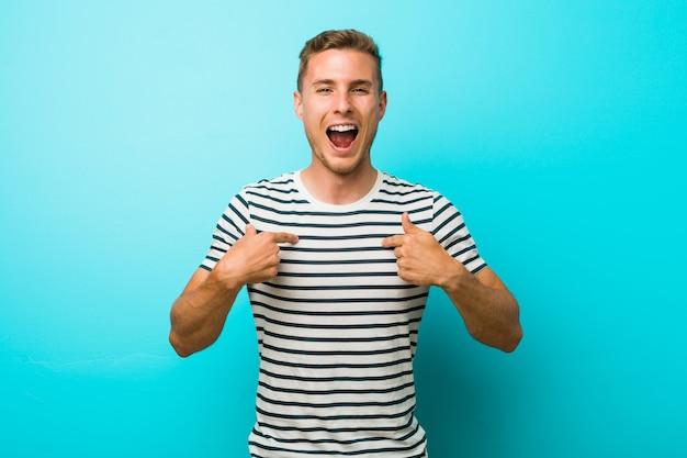 水色の壁に対して若い白人男は指で指を驚かせて、広く笑っています。
